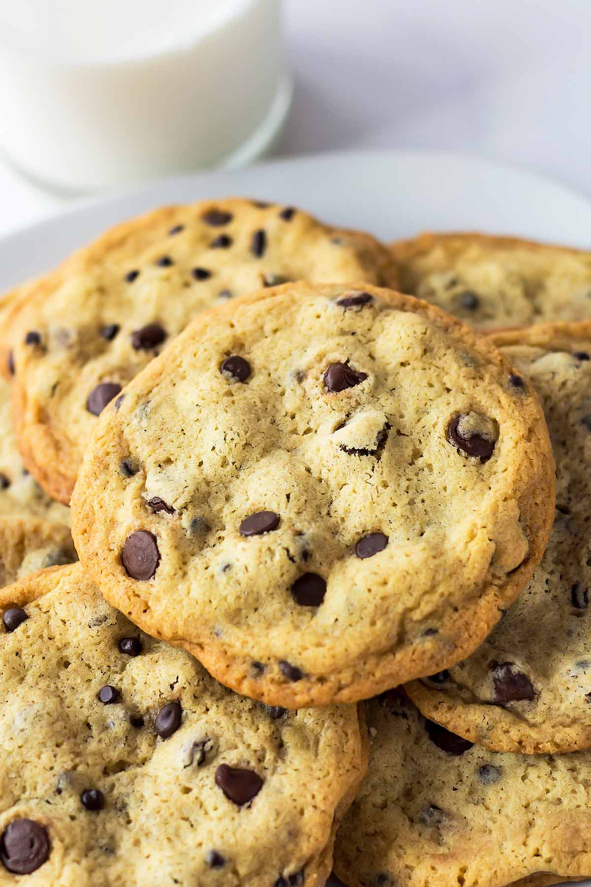 The best chocolate chip cookies on a plate with milk class in back