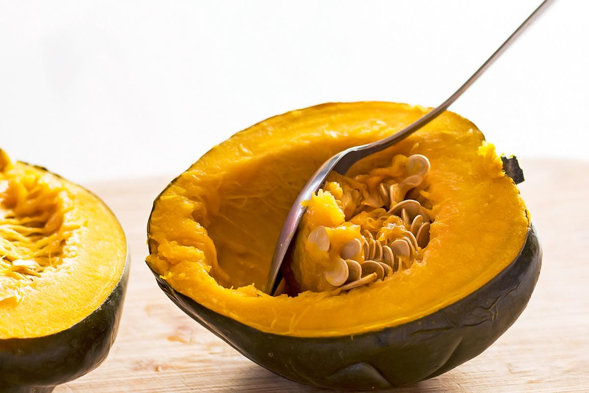 Scooping seeds from acorn squash half